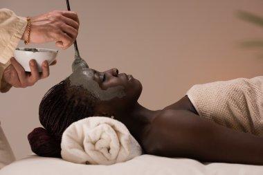 Beautician applying mud mask to woman
