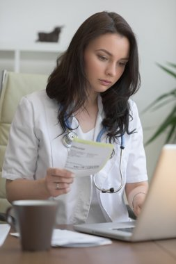 Doctor working with test results and computer