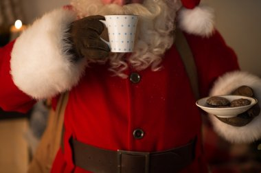 Santa Claus eating cookies and drinking milk