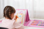 Small girl artist with pigtails posing backwards to camera and painting, child drawing house, uses colored pencils and wax crayons, dresses casually, sitting at table.