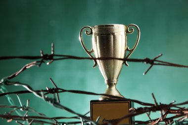Golden trophy in barbwire