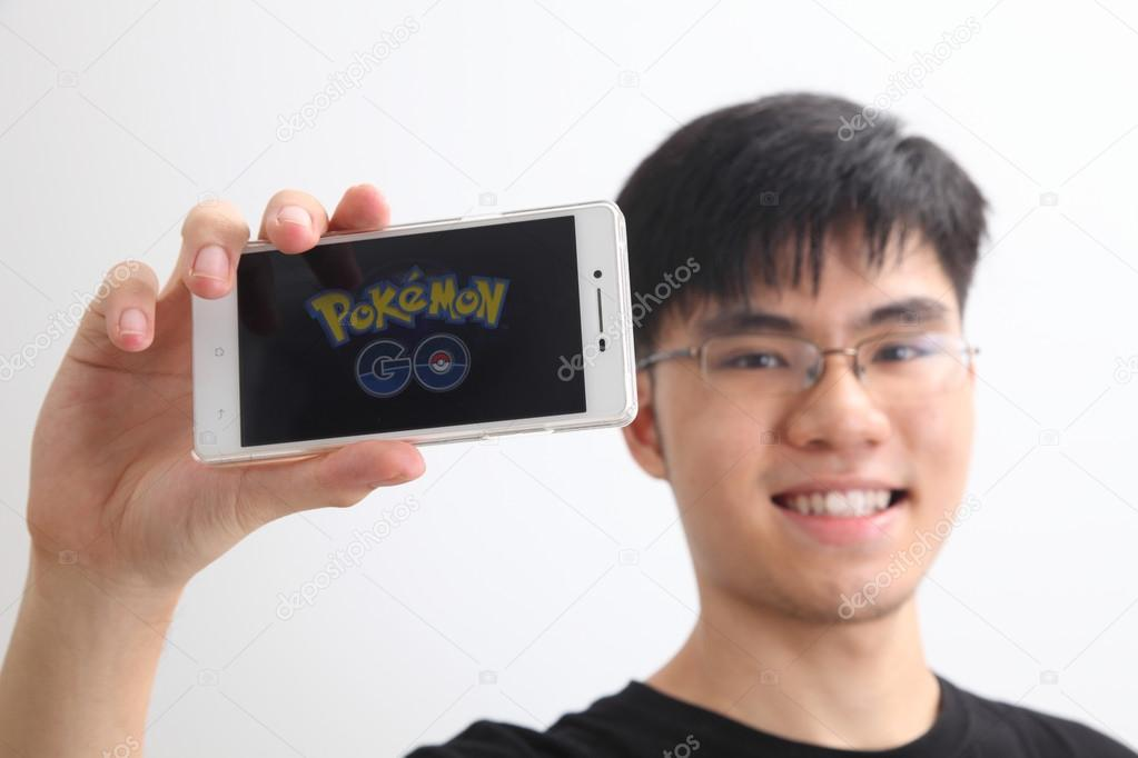Teenager holding a smartphone with Pokemon go