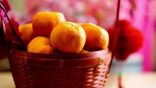Kosár mandarin narancs és kínai újév fesztivál dekorációk, piros csomag, szilva virág, ingot és lámpás piros alapon.