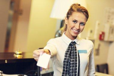 Pretty receptionist giving key cardreceptionist giving key card