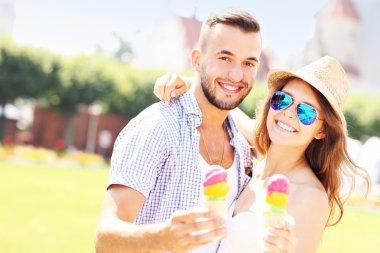 Joyful couple eating ice-cream cones