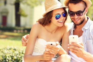 Joyful couple using smartphones in the park