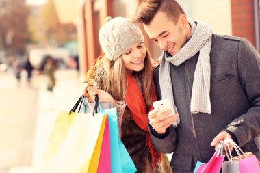 Mutlu çift smartphone ile şehirde alışveriş