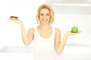 Happy woman with donut and apple
