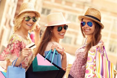 happy friends shopping in the city