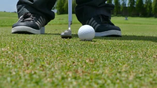 Golfový hráč s jeho putt na zelené golfové hřiště