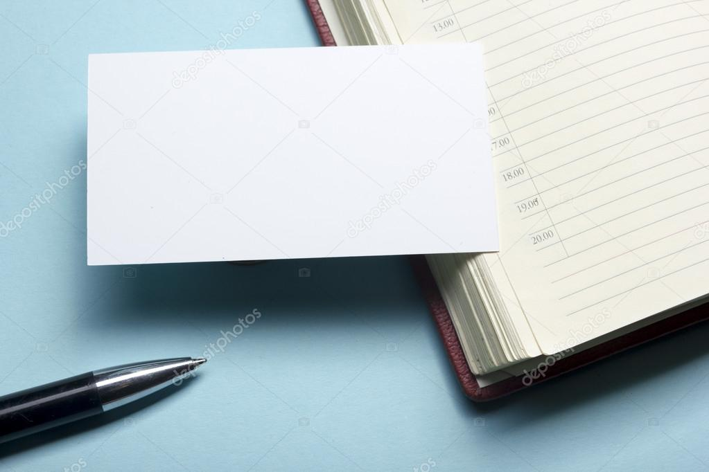 Business card blank over notepad at office table. Corporate ...