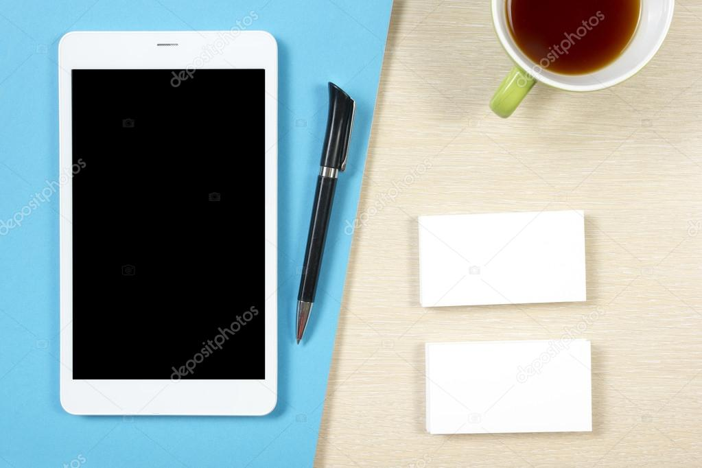 Business card blank, smartphone or tablet pc, coffee cup and pen at ...