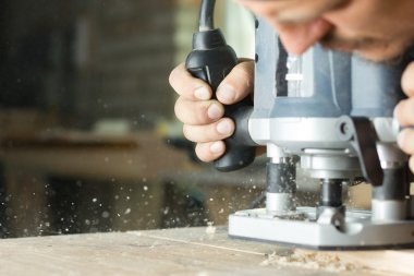 Close-up of carpenter cutting a wooden plank. Selective focus. Copy space