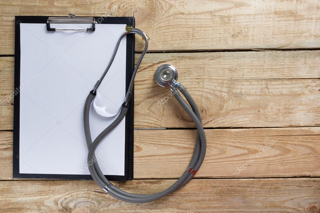 Stethoscope and clipboard on wood table top view . Medical background. Concept for diet, healthcare, nutrition or medical insurance