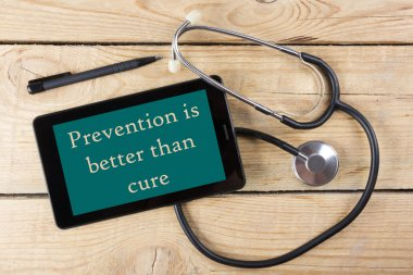 Prevention is better than cure - Workplace of a doctor. Tablet, medical stethoscope, black pen on wooden desk background. Top view