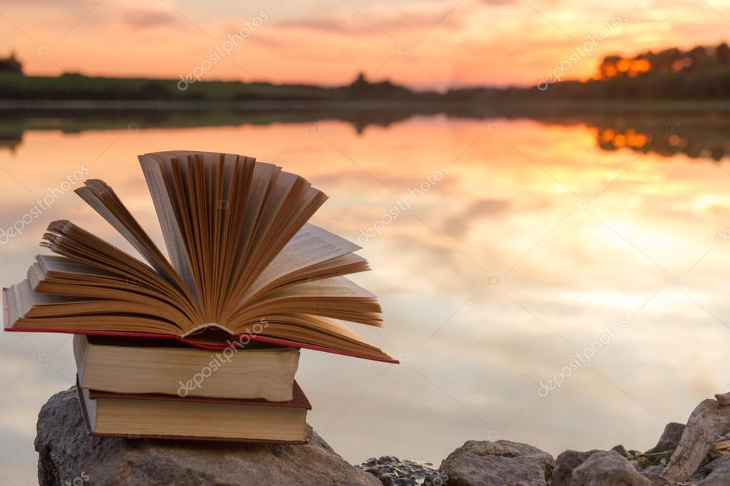 Stack of  book and Open hardback book on blurred nature landscape backdrop against sunset sky with back light. Copy space, back to school. Education background.