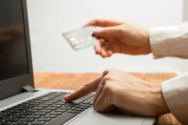 Hands holding credit card typing numbers on tablet pc making online payment at home the wooden table. Online shopping concept. Selective focus.