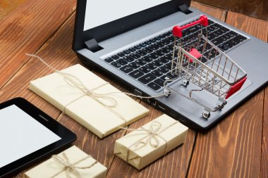 Online shopping concept - Empty Shopping Cart, laptop and tablet pc, gift box on rustic wooden background