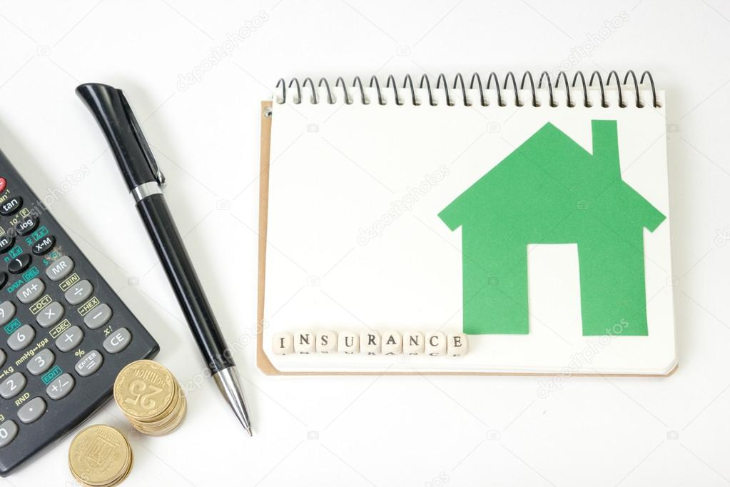 Concept of housing purchase and insurance. Office desk table with supplies top view. Calculator. golden coins, pen, notepad, green model house, wooden block word