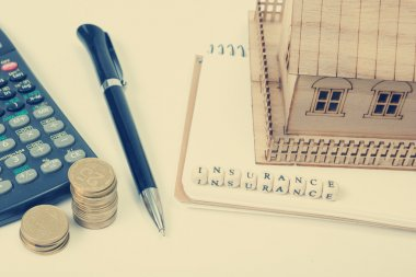 Concept of housing purchase and insurance. Office desk table with supplies top view. Calculator. golden coins, pen, notepad, model house, wooden block word