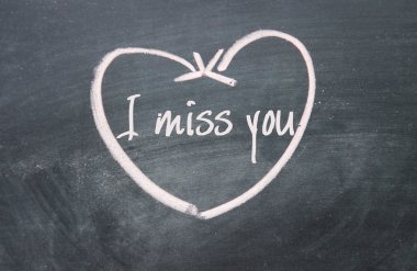 I miss you text and heart sign on blackboard