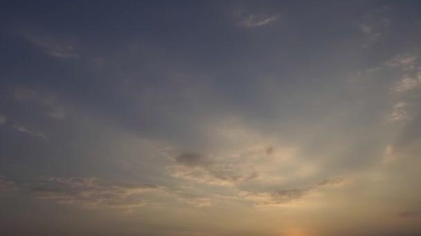Die Sonne geht vom Horizont auf. Schöne Wolken fliegen in den blauen Himmel. Rollende geschwollene Wolken bewegen sich. 4K-Zeitraffer