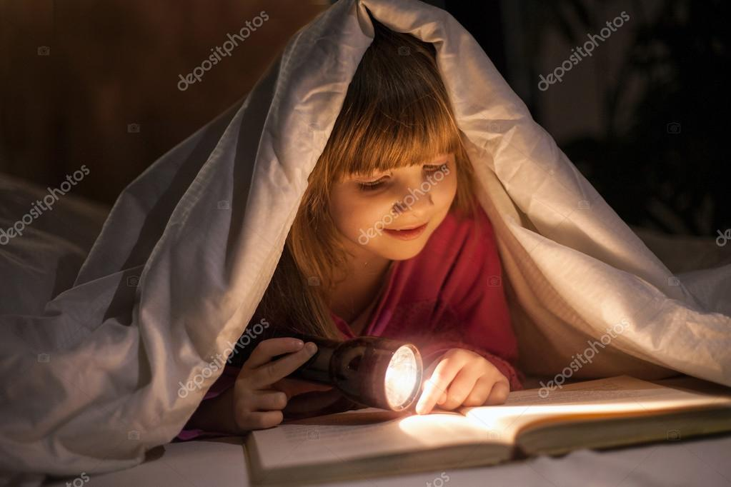 A young girl reading a book under the covers with a flashlight