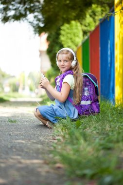 young girl sitting next school fence and listening to music