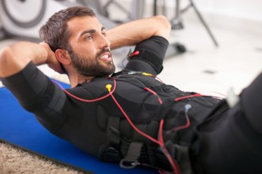 young fit man exercise on  electro muscular stimulation machine