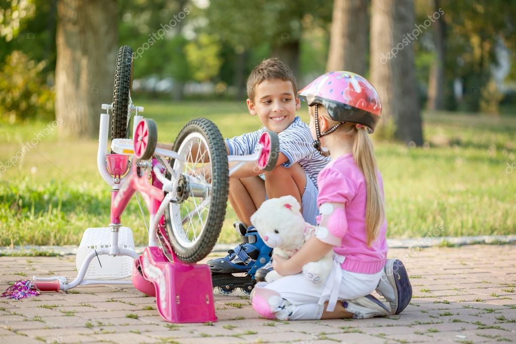 Boy on roller skates helping sweet little girl to repair the bik