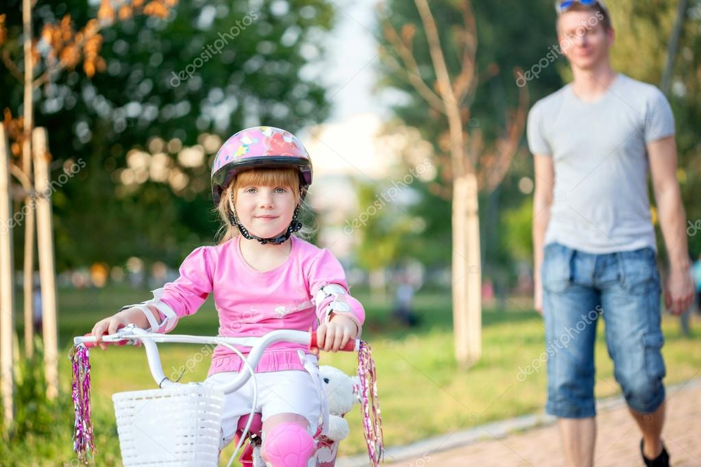 Father teaching his daughter to ride a bike
