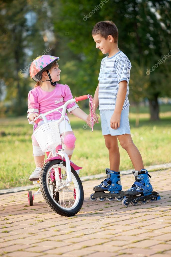 Brother and sister outdoors riding bikes and roller