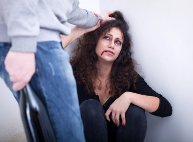 Despaired woman beaten by drunk man. concept of home violence