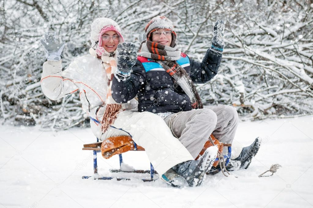 winter fun, boy and a girl sledding at winter time