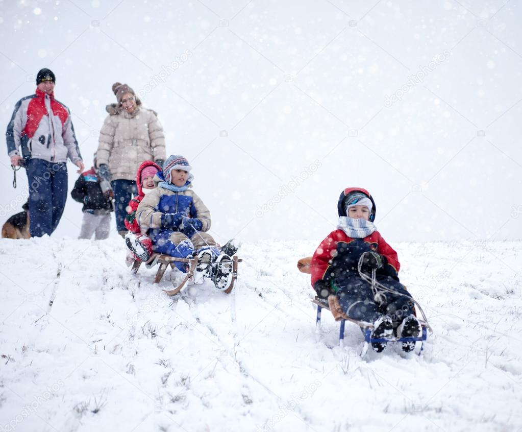 mom, dad with kids having fun in the snow