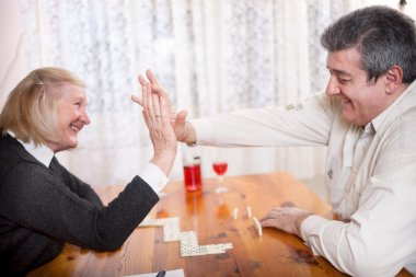 happy senior people in retirement home playing domino game