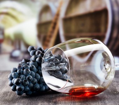 Wine glass with grape on wooden table