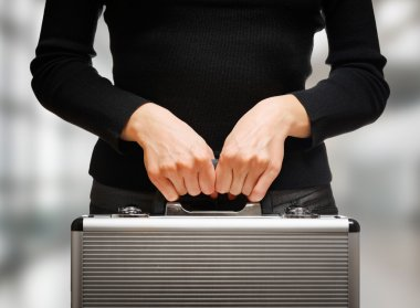 Business woman holding an aluminum briefcase and preparing for i