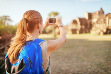 Female tourist taking picture of Angkor Wat temple, Cambodia
