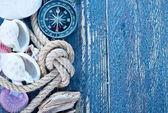 Fotografie Mořské mušle a kompas na stůl
