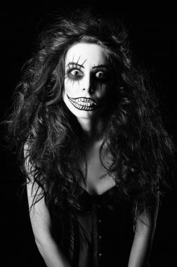 Beautiful young woman in the image of sad gothic freak clown. Black and white