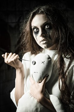 Horror style shot: scary monster girl with moppet doll and needle in hands