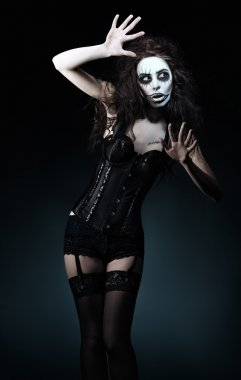 Beautiful young woman in the image of sad gothic freak clown