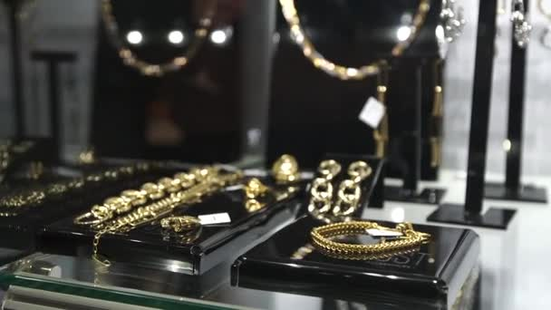 Beautiful jewelry on store shelves shimmer in different colors in rays of light. Closeup.
