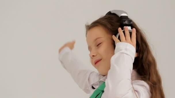Portrét holčička ve sluchátkách poslouchat hudbu a tanec. Zpomalený pohyb
