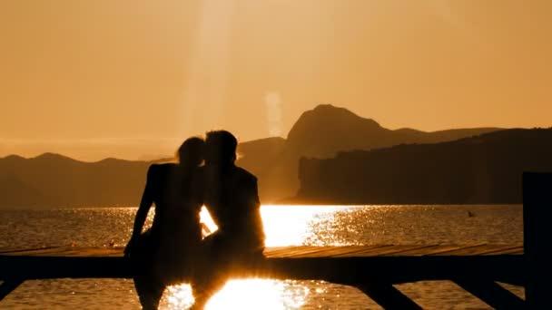 Man and Woman Sitting On Bridge At Sunset
