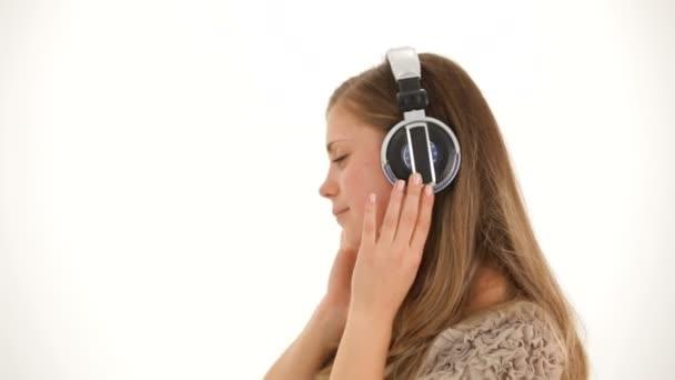 Mladá krásná žena v sluchátka poslouchat hudbu a tanec