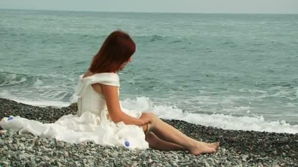 Krásná žena nosí punčochy, sedí na pláži