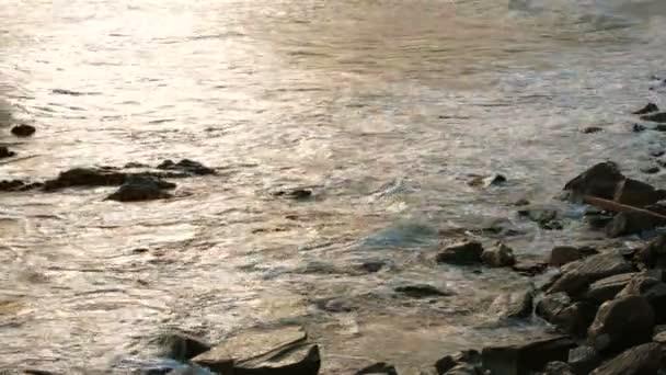 Mořské vlny jemně mytí Rocks při západu slunce. Zpomalený pohyb