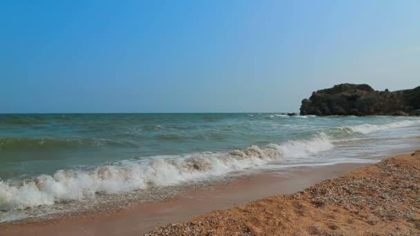 Mořské vlny a modrá obloha na pobřeží. Zpomalený pohyb.